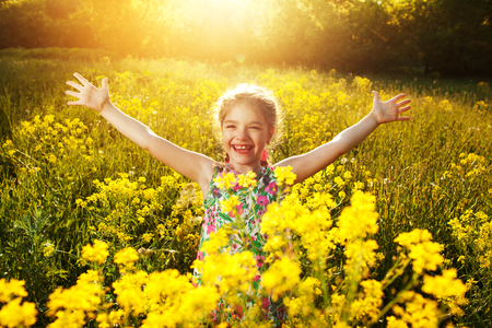 Happy cheerful little girl among yellow wildflowers Banque d'images