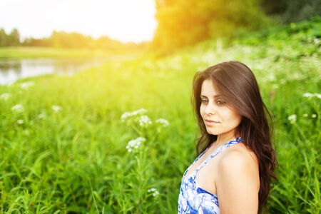 Beautiful dark-haired girl in the middle of a green meadow