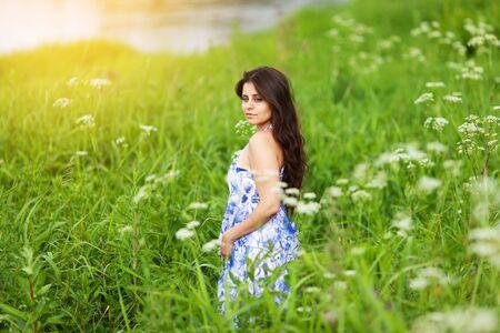 Beautiful sweet girl in blue dress among wildflowers