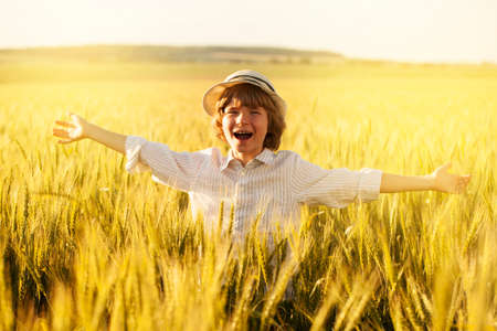 Happy boy with hat in the middle of wheat field