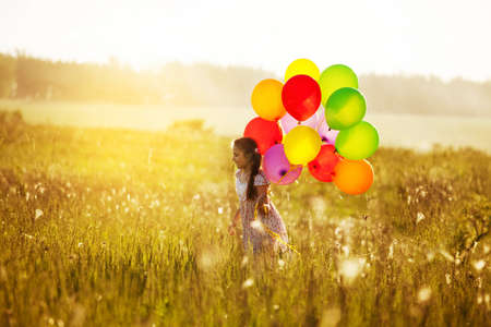 Happy girl with balloons walking across the field at sunset Stock Photo