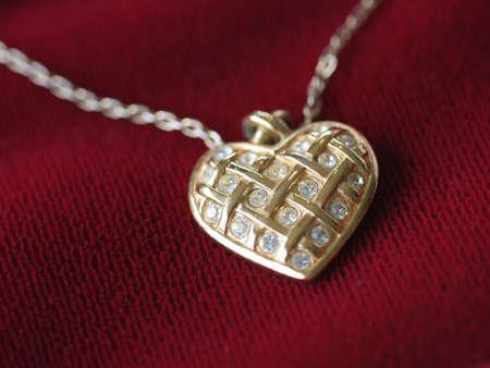 赤いベルベットの金と偽ダイヤモンド ハートネックレスのクローズ アップ。 写真素材