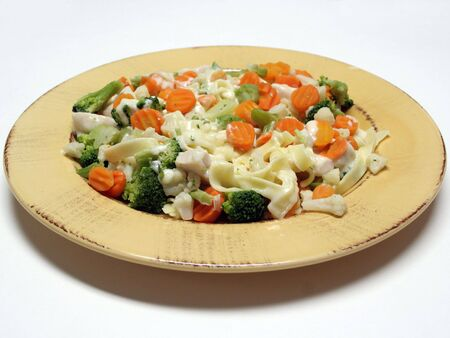 Plate of fettucine alfredo with chicken and steamed vegetables