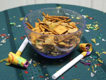Close up of party blowers on a teal tablecloth, with snack mix and confetti photo