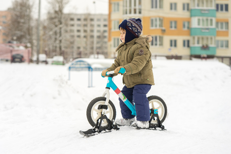 Boy on bike with skis preparing to move down from the mountains Stock Photo