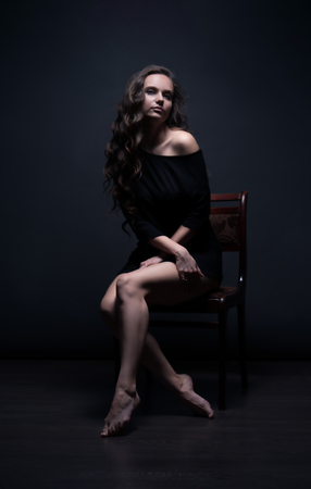 Young beautiful girl poses sexually on a black background