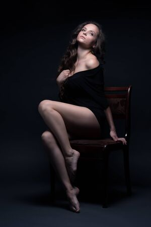 footsie: Young beautiful girl poses sexually on a black background