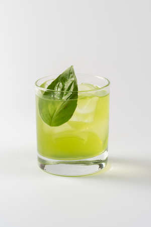 Alcoholic cocktail with basil in glass goblet on white background