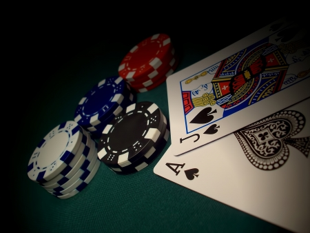 Red, blue, white, black poker chips on a green felt gaming table. Two cards and chips are spotlighted.  Jack of Spades and Ace of Spades gives a Blackjack winner.