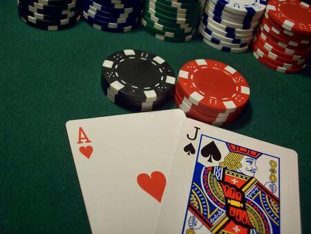 Jugador obtiene Blackjack con una gran apuesta en la tabla. Rojo, negros, azules, verdes y blancos chips en una mesa de p�quer verde - el as de corazones y la Sota de espadas da un Blackjack.  Foto de archivo - 9739260