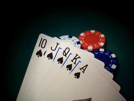 royal: Closeup of a Spades Royal Flush poker hand overlooking a green table with white, red, and blue chips highlighted by a spotlight. This hand cannot be beat.