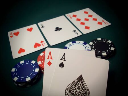 Three cards face up and multi-colored poker chips on a green felt table. This is known as The Flop in the popular poker game Texas Hold 'Em. The player is holding two Aces and another one on the table, a very good hand. Bet high! Redakční
