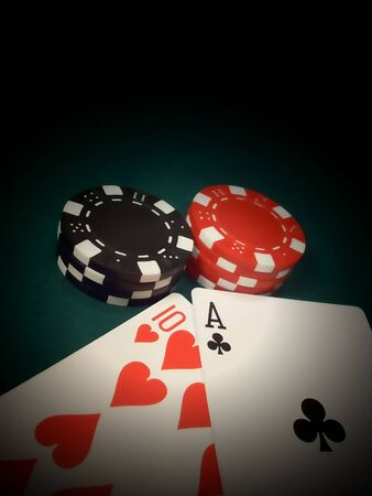 best hand: fichas de p�quer de rojo y negro pasar por alto el diez de corazones y el as de los clubes en una mesa de fieltro verde haciendo 21, la mejor mano en blackjack. r�pida y flexible. Foto de archivo