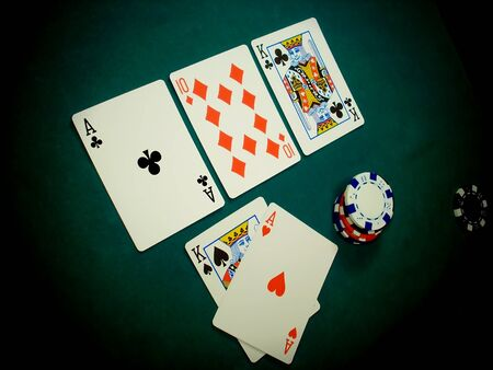 Angled view of a TEXAS HOLD EM hand. This stage of the game is known as THE FLOP, three cards dealt face up on the table (ACE KING TEN). The player has thrown his two HOLE CARDS face up on the table (KING ACE) because he is ALL IN with a pretty good hand