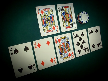 A Pai Gow Poker hand is spotlighted against a poker green background showing the hand on top as a Pair-Of-Jacks and the bottom hand as Three-Fours... a very good hand and hard to beat. Pai Gow Poker is also called Double-Hand Poker and is very popular in
