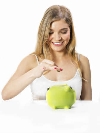 Pretty girl putting  coins in moneybox photo