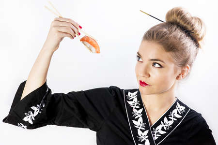 Pretty girl in black japanese dress eating with sushi stick on white background