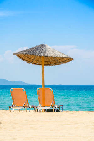 Holiday two sun beds on sand next to the sea portrait Stock Photo