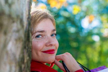 woman looking behind tree Stock Photo