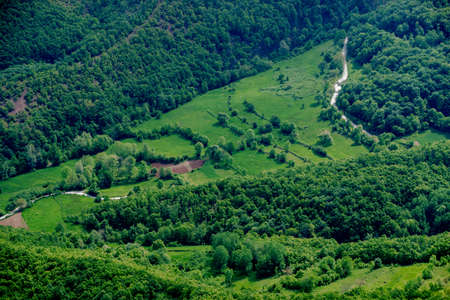 Aerial view on beautiful green valley with road Stock Photo