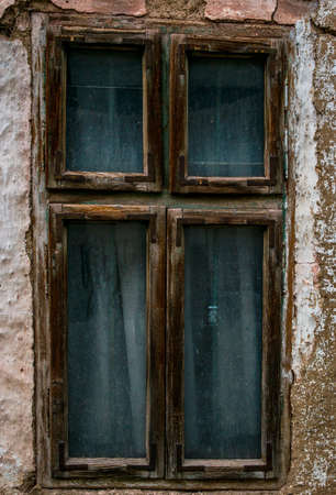 Abandoned old window with blue curtain on cracked wall