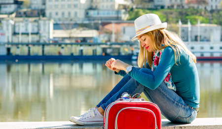 Young woman with hat sitting on the dock Stock Photo