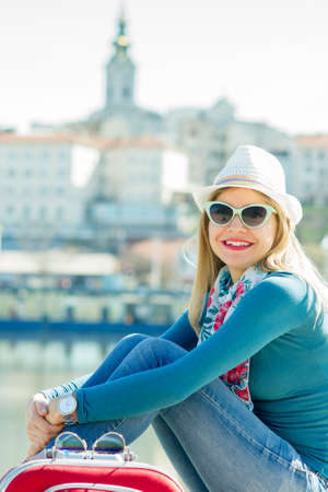 Young smiling woman with sunglasses and hat sitting by the river