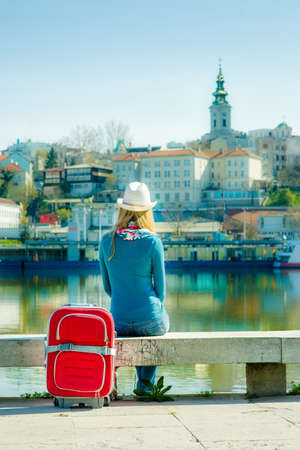 Young woman with suitcase sitting on the dock and looking at the city by river