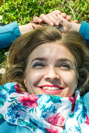 Young woman with scarf lying on the grass in park