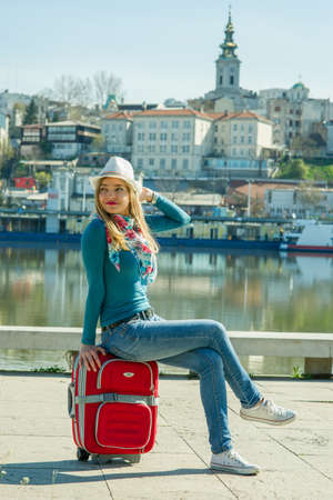 Beautiful young woman sitting on the red suitcase Stock Photo