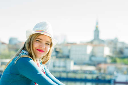 Young smiling woman with hat looking at camera and city behind her