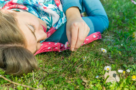 Young woman lying on the grass in park and picking up a flower Stock Photo