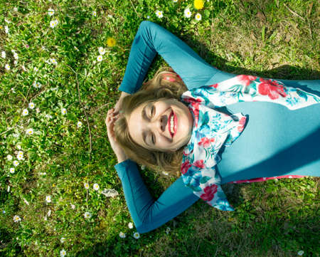 Young smiling woman lying on the graas in park