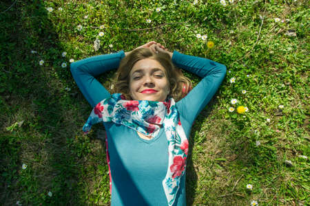 Happy young girl lying on the grass with flowers all around her