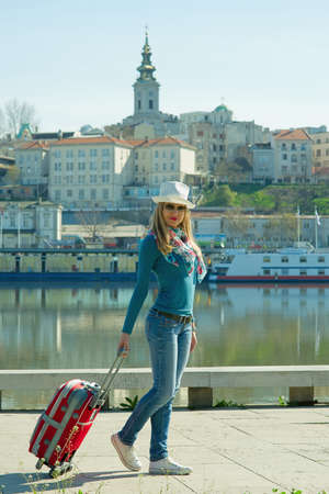 Young girl with hat and sunglasses pulling a suitcase