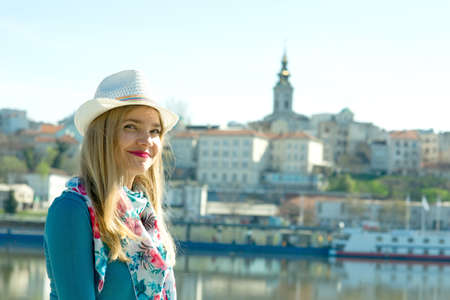 Smiling girl with hat and scarf standing by the river