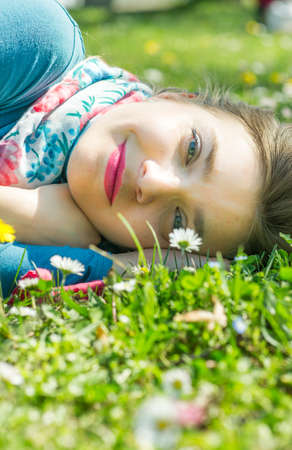 Beautiful young woman lying on the grass and looking at camera with her blue eyes