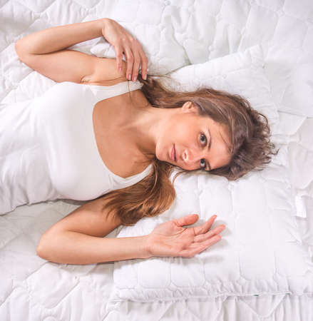 Attractive ypung woman lying on soft pillow Stock Photo