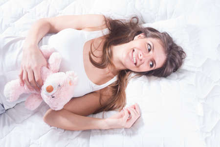 Young smiling woman with teddy bear in bed