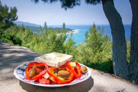 Greek salad on white plate with red tomato and white greek cheese and turquoise sea and coast in bacground