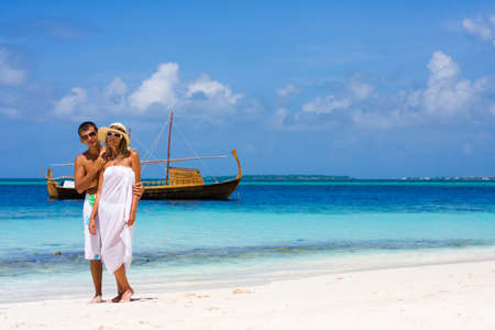 Young couple on a beach on a background a yacht photo