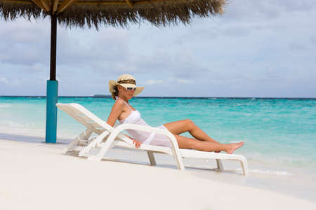 Lady relaxing in the chaise lounge on a exotic resort photo