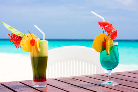 Two cocktails on a table at shore of ocean photo