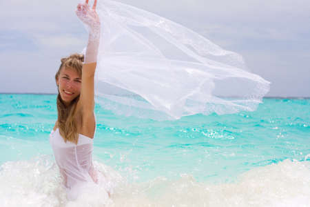 Bride on a coastline at tropical beach photo