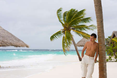 Young man on a tropical beach in the morning during a gale photo