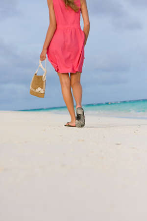 Girl goes for a walk on the coast of tropical island photo