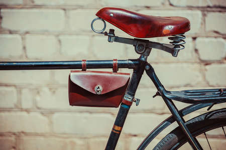 wornout: Photo old vintage bike, which stands near the brick wall. Close up of an old, worn-out bicycle frame in which leather, vintage, shabby brown seat, glove compartment. Behind is the trunk. Stock Photo