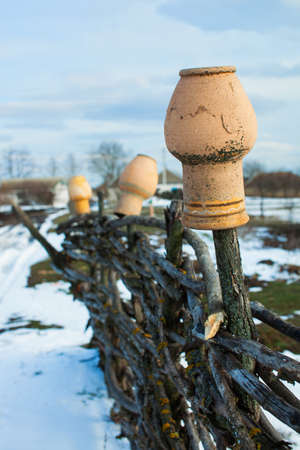 winter thaw: In the old wicker fence hanging pitchers. Rural farm. End of winter thaw. Stock Photo