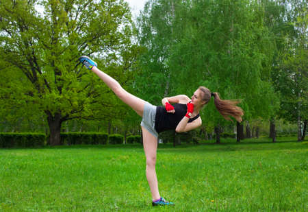 Beautiful kick boxing girl carries a high kick. Outdoors. in the park. Reklamní fotografie
