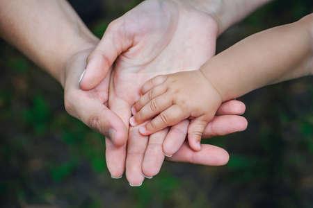 Drie handen van dezelfde familie - vader, moeder en baby blijven bij elkaar. Detailopname. Het concept van eenheid in het gezin, bescherming, ondersteuning, welvaart, liefde en ouderlijk geluk.